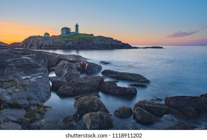Nubble Head Lighthouse with smooth water and golden color