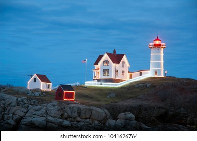 Nubble lighthouse, also known as Cape Neddick light, is decorated and lit up at dusk during the holiday season in Maine. It is a favorite attraction for tourists.