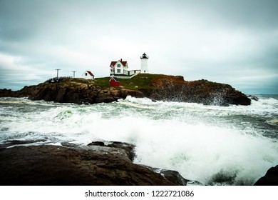 Nubble Lighthouse in York, Maine on cloudy day with storm waves crashing on rocks.