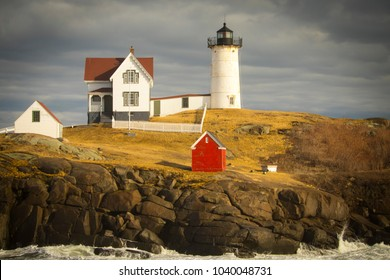 The Nubble Lighthouse in York, Maine under dark storm clouds. A pastoral New England seascape and a truly classic lighthouse, Cape Neddick, Maine, USA.