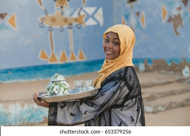 A Nubian girl carrying a teapot