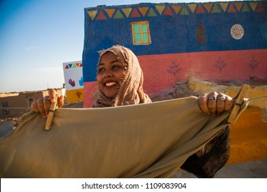 a Nubian girl hanging her laundry in a village in aswan