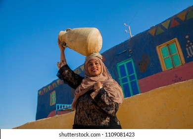 a Nubian girl holding a nile water pot in village in aswan
