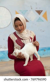 Nubian Young Lady Cuddling a Cat