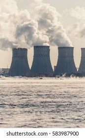 Nuclear or atomic power plant or NPP. Cooling towers with thick smoke and cooling pool. Vertical photo
