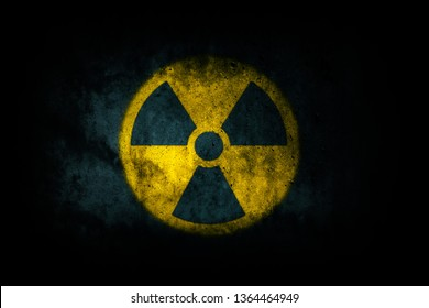 Nuclear energy radioactive (ionizing atomic radiation) round yellow symbol shape painted on massive concrete cement wall texture dark background. Nuclear radiation or radioactive alert warning danger.