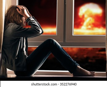Nuclear explosion. girl girl sitting on the window. She covered her face. Outside, explosion, mushroom cloud. A teenager in jeans, barefoot.