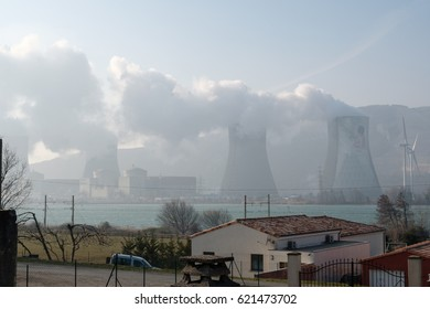 nuclear power plant in Cruas, France produces steam from reactors; in front river Rhone, railway and house