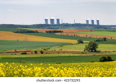 Nuclear power plant on horizon of spring landscape with flowering spring fields. Czech Republic, Europe.