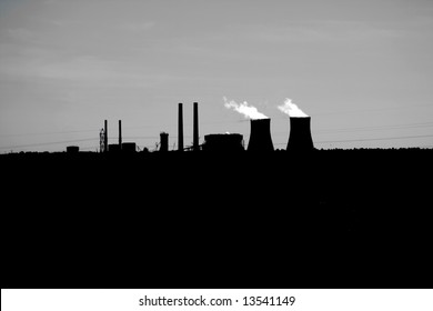 Nuclear Power Plant Silhouette captured in Florida in the United States. Steam or Smoke is shown coming from the top of the stacks which are on the horizon.