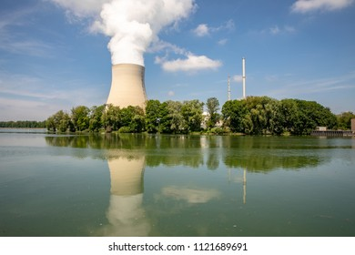 Nuclear power station with funnel, reactor dome and huge cooling tower steaming on the far side of a wide river with a beautiful reflection on the water surface and almost clear blue sky.