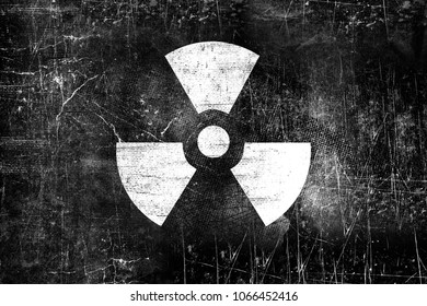 Nuclear radiation sign on old grungy wall. Symbol of radiation contamination. Monochrome black and white vintage illustration