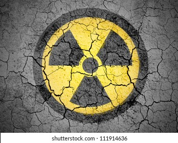 Nuclear radiation symbol painted on cracked ground with vignette