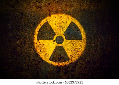 Nuclear radioactive (ionizing radiation) round yellow danger symbol painted on a massive rusty metal wall with dark rustic grungy texture background with vignetting