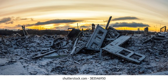 Nuclear winter.The remains of destroyed houses covered with snow at sunset