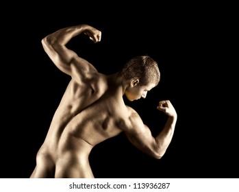 Nude athletic man posing in gold skin make-up