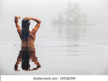 Nude back of middle aged Caucasian woman bathing  and washing hair in Maine lake on a foggy Summer morning.