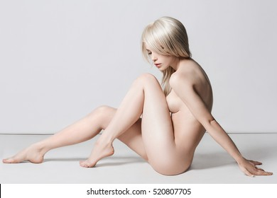 nude beautiful blond woman. naked sexy girl with perfect body sitting on the floor