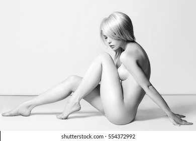 nude beautiful blond woman. naked sexy girl with perfect body sitting on the floor.black and white fashion portrait