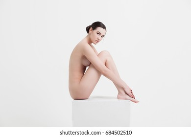 nude beautiful sensual woman. naked sexy girl with perfect body sitting on the cube