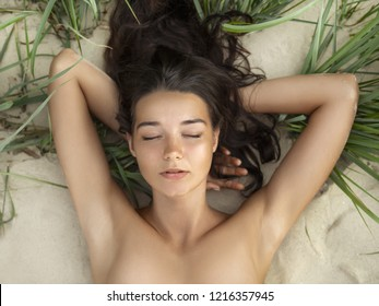 Nude beautiful woman on the nudist beach. Lady with nude perfect body laying on sand. Gorgeous mixed race Caucasian Asian girl posing on travel vacation holidays naked outdoors. Close-up portrait of