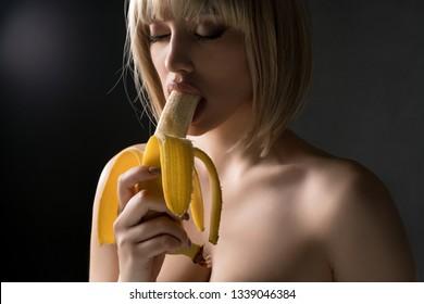 Nude blonde eating banana shot
