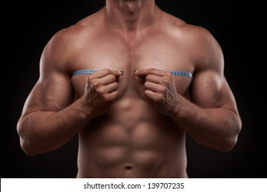 Nude bodybuilder with a measuring tape around his chest isolated on black background