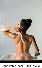Nude brunette with massage brush rearview in bath