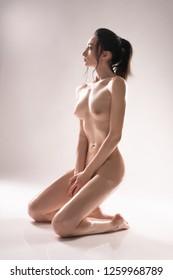 Nude brunette sitting on her knees shot