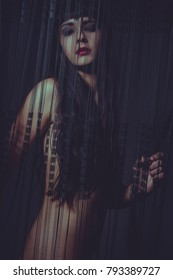 Nude brunette woman behind a curtain of black and thin threads with sensual look