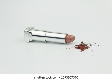 Nude color lipstick with red color powder on isolated white background