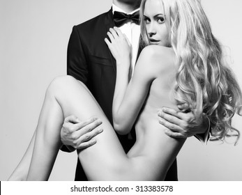 Nude elegant lady at the hands of a young man in suit