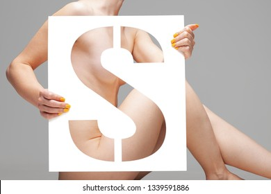 nude female body behind stencil letter s