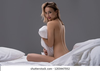 Nude girl sitting on her bed rearview