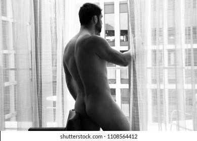 Nude good looking man shows his backside and butt, bottom, as he stands in front of curtains of the balcony of his hotel room