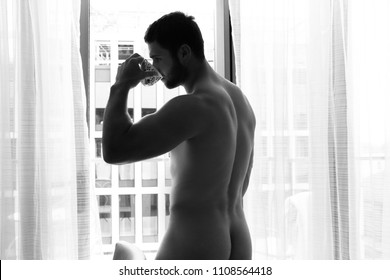 Nude good looking man shows his backside and butt, bottom, as he stands in front of curtains of the balcony of his hotel room, drinking tea