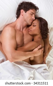 nude heterosexual couple in bed peacefully sleeping in embracing each other in hug. Mid adult Caucasian men in late 30s and young black African-American woman in 20s