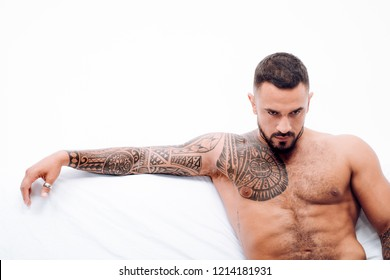 Nude male model lies in white bed. Muscular tattooed Man ready to St Valentine's Day. Muscular man alone in bed - Happy Valentine's Day