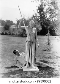 Nude man outside with statue of woman with spear