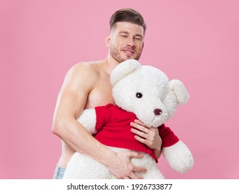 nude men hugs a toy polar bear on a pink background and holidays on march 8