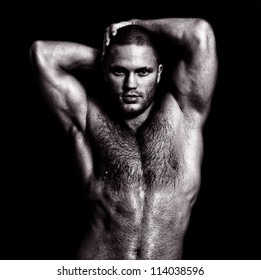 Nude muscular guy posing with hands behind head. Black and white