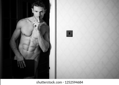 Nude muscular man covers his modesty with book while holding a finger to his lips