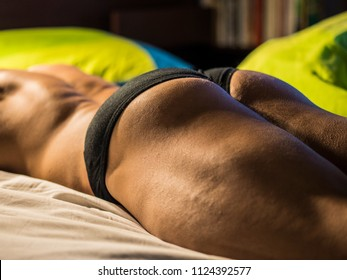 Nude muscular man with perfect body posing on bed in soft light.
