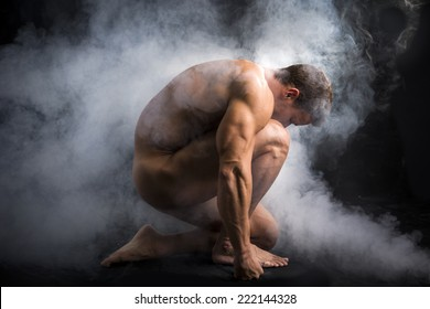 Nude Profile of Young Muscle Man Crouching in Fog in Studio with Black Background
