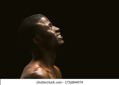 Nude sexy african guy looking up Coffee Space on the right side. Profile portrait of Afro American man looking upwards on black background.
