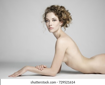 nude sexy beautiful woman with long stylish hairstyle pose on white background in photostudio. Erotic portrait of elegant nude lady with perfect naked body. Sexual photography of young nude blonde.