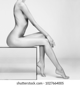 nude sexy beautiful woman with perfect figure pose on white background in photostudio. Erotic portrait of elegant nude lady with  naked body. Sexual photography of young nude blonde. Sensual model.