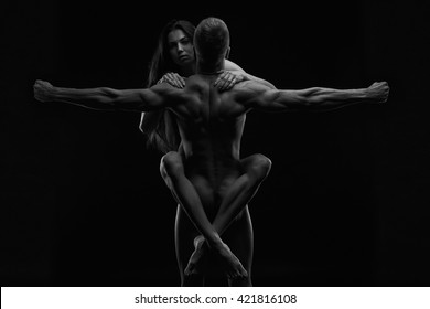 Nude sexy couple. Art photo of young adult man and woman. High contrast black and white muscular naked body on black background