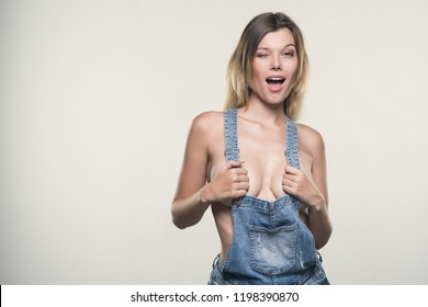 Nude sexy girl with big breasts in jeans jumpsuit on white background
