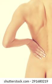 Nude slim woman with backache